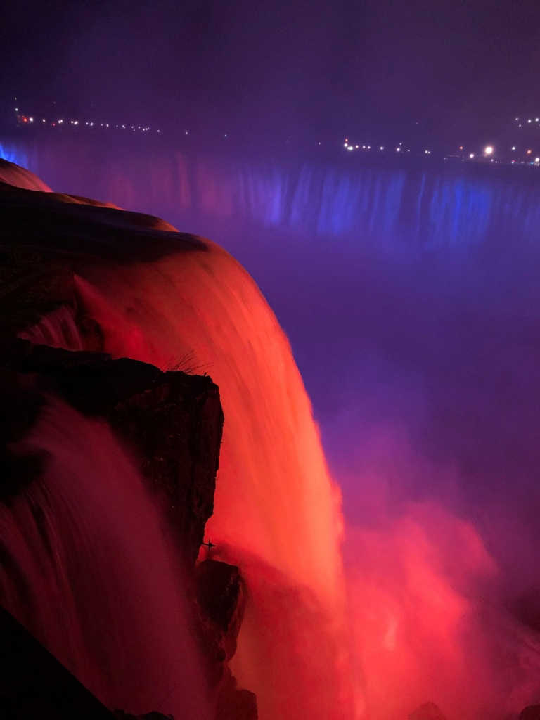 Niagra Falls lit up in orange and blue lights