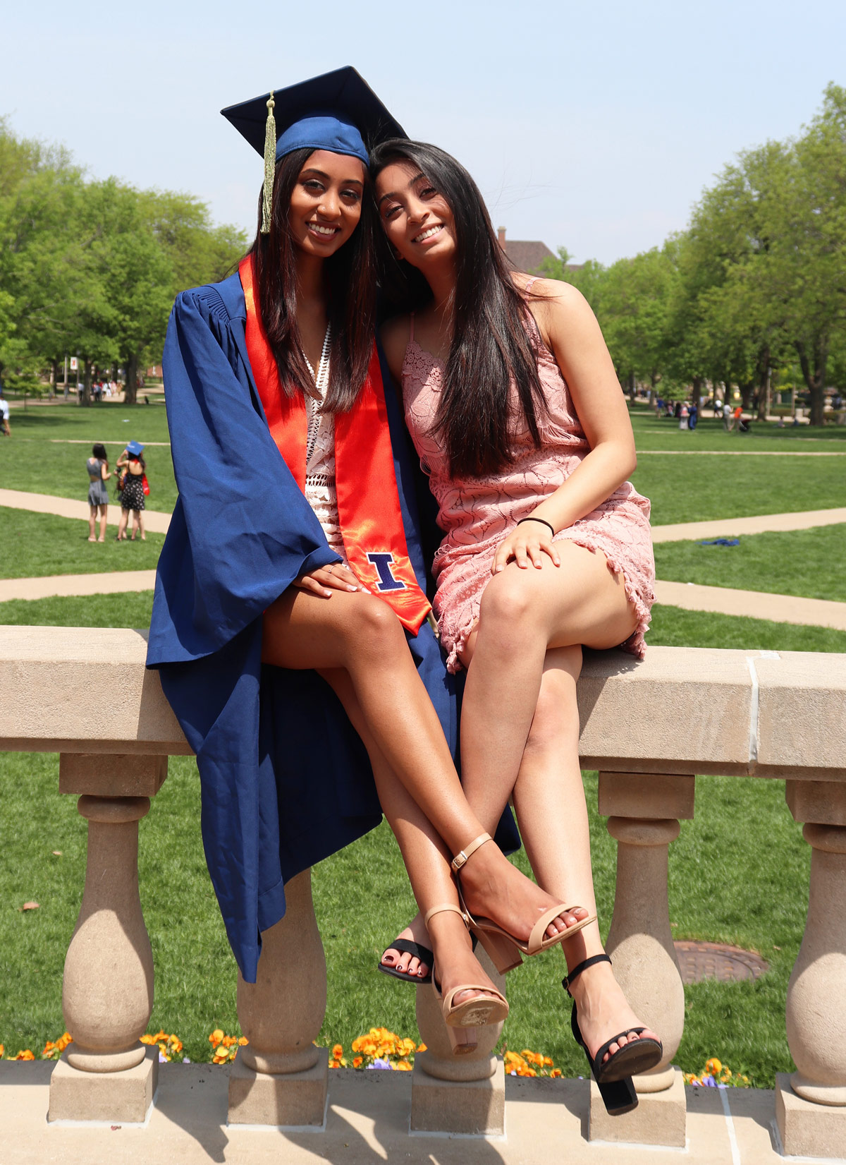 Swathi posing with her sister in graduation cap and gown