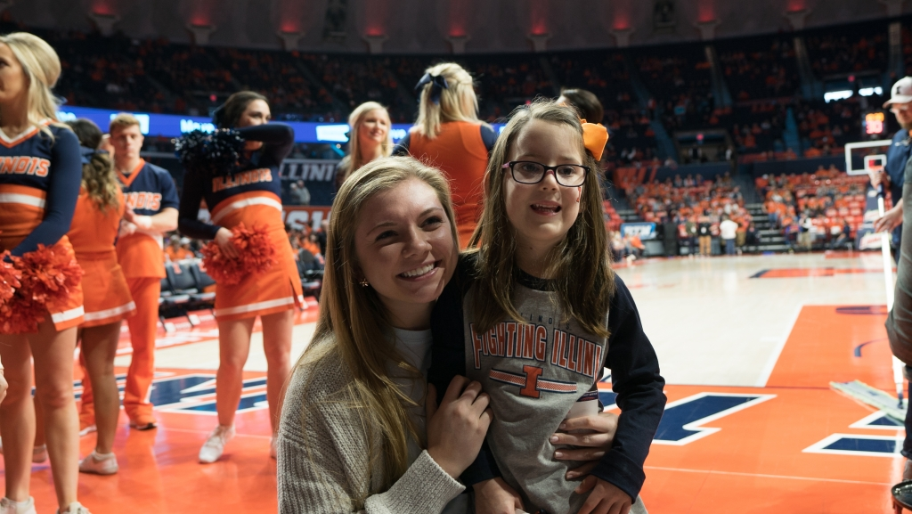 Rachel on the State Farm Center's court posing with little girl