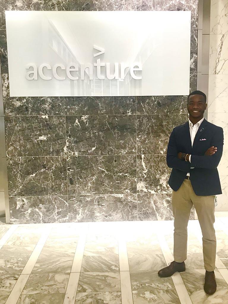 Taofik standing next to an Accenture sign.