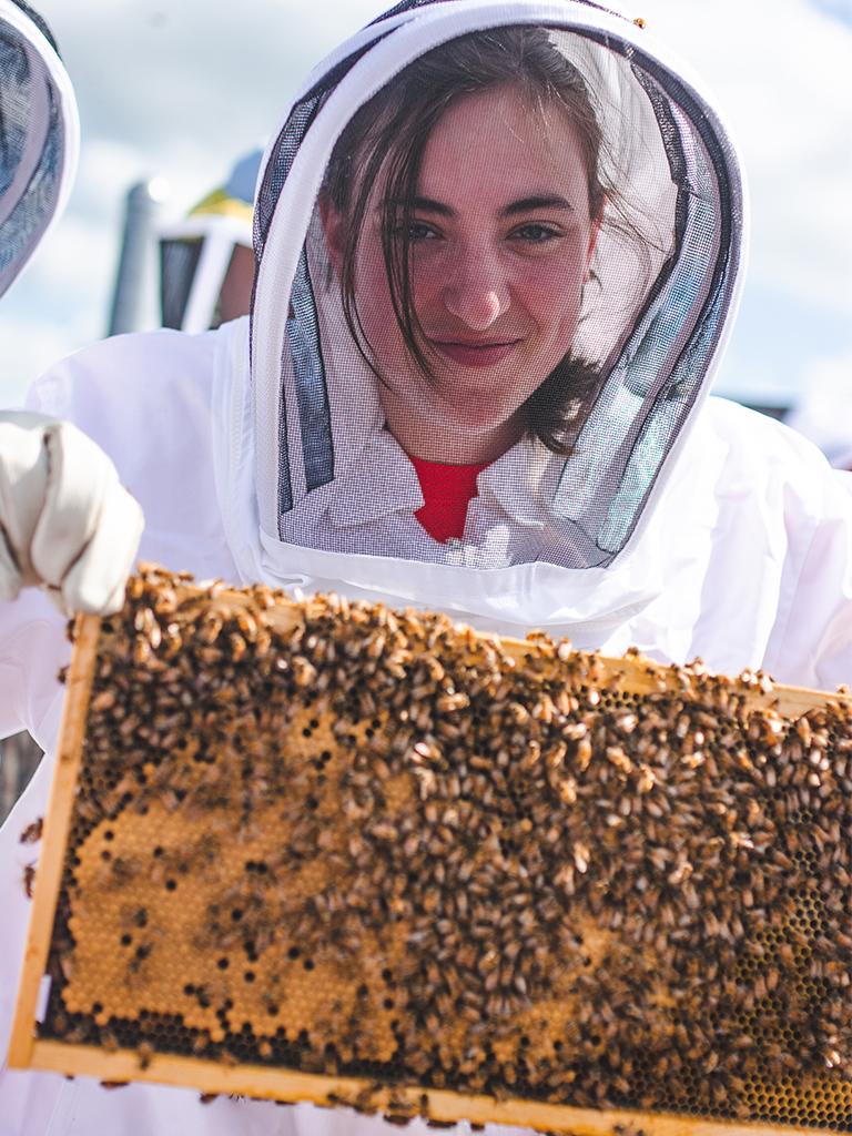 Beekeeping Club Member poses with bees.