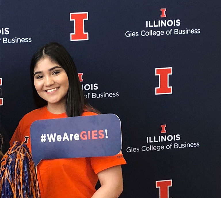 """Andrea posing with a sign that reads """"#WeAreGIES!"""""""