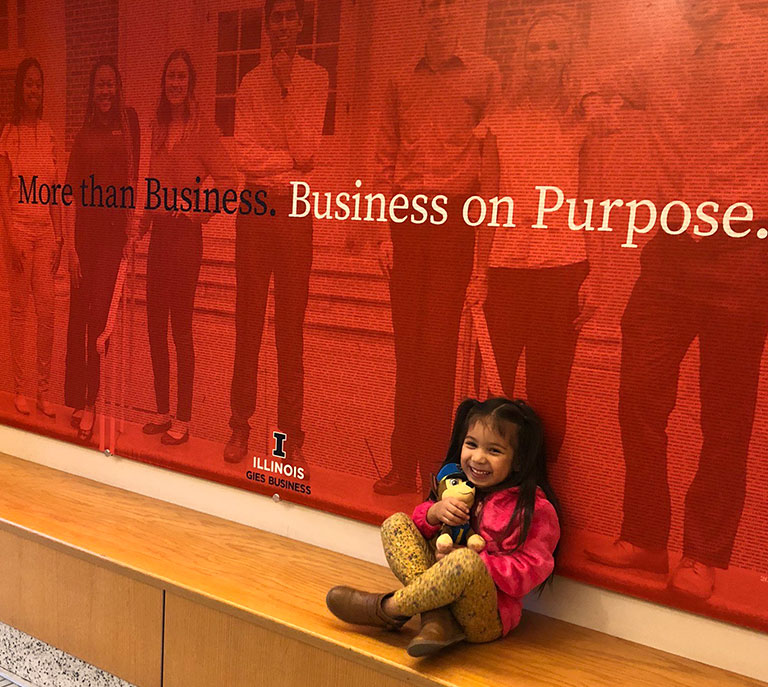 """Andrea's four-year-old daughter sitting in front of an on-campus sign that reads, """"More than Business. Business on Purpose."""""""