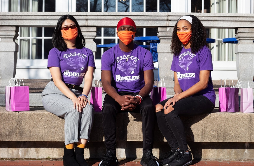 Hannah, Janina, and David pose together outside the Illini Union wearing Health of the Homeless shirts