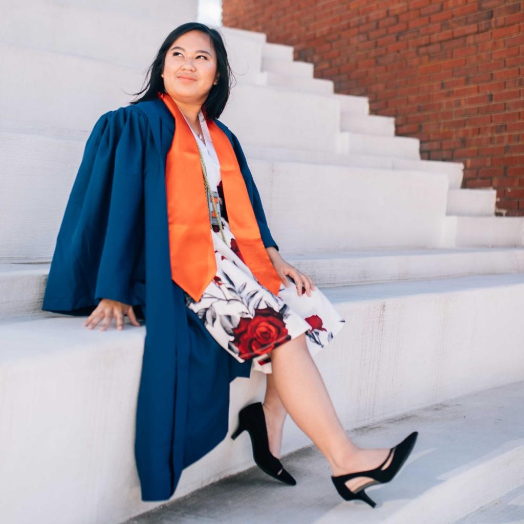 Cherish on the steps of the Krannert Center for Performing Arts in graduation regalia.