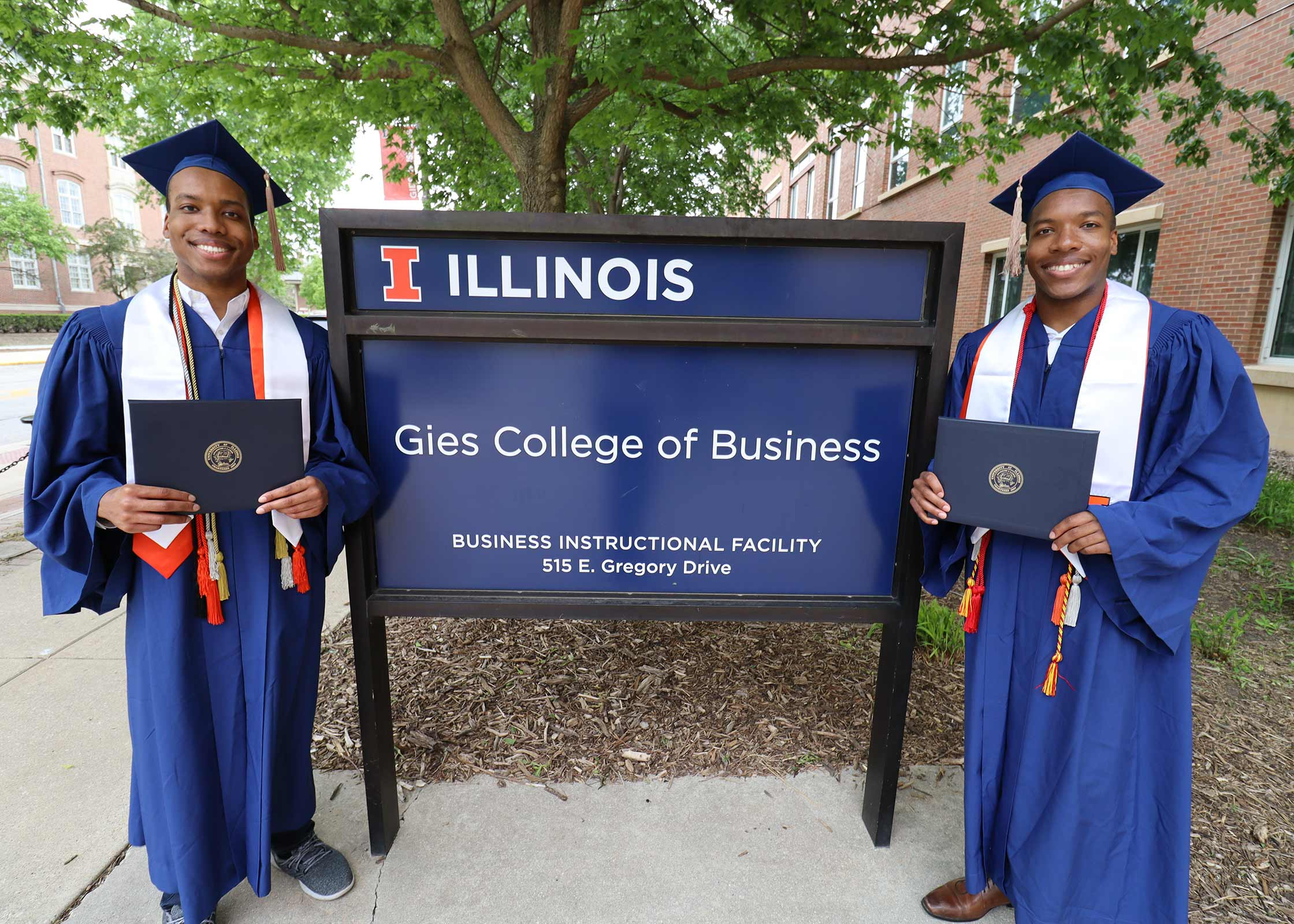 Michael (right) and his brother Robert (left) posing in front of the GIES College of Business sign after Michael's graduation.